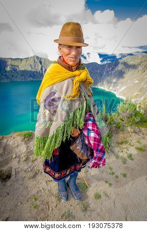 QUITO, ECUADOR - NOVEMBER, 25 2016: Unidentified indigenous old woman wearing a typical andean clothes in front of the Quilotoa lake with a beautiful magenta color of the Quilotoa caldera. Quilotoa is the western volcano in Andes range and is located in a