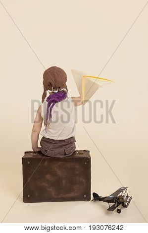 Kid holding paper airplane on antique suitcase isolated.