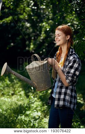 A woman in the garden holds a watering can, a gardener, summer.