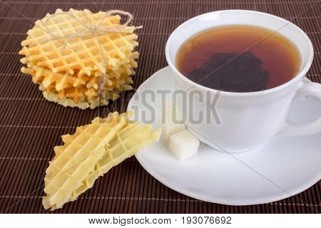 Breakfast With Waffles, Black Cup Of Tea And Pieces Of Waffle On Wooden Surface