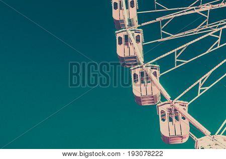 Ferris wheel on blue sky copy space. Vintage