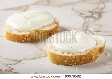 Sesame bagel with cream cheese and salt on table