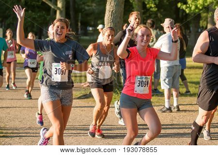 Two young women waving at my camera during the Belmont lake Summer series running race. The race was held on Monday June 26 2017 at Belmont Lake State Park New York.
