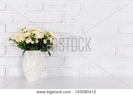 Flowers On The Table Over White Brick Wall
