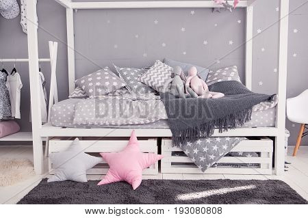 A cot-house. On the bed is a plaid with cushions and toy hares. Interior in white and gray tones