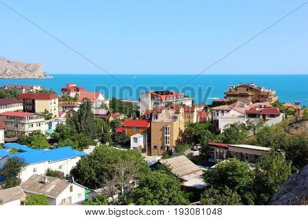 Resort town with views of the sea and cliffs in the summer on a Sunny day. Landscape. Sudak, Crimea, Russia.
