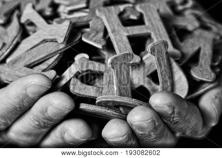 closeup of the hands of a young caucasian man holding a handful of different wooden letters, in black and white