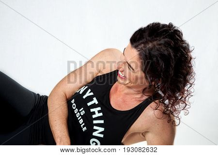 Laughing athletic woman leaning on her elbow. Her eyes are closed and she is enjoying life. On white background enjoyment leaning curly hair encouraging