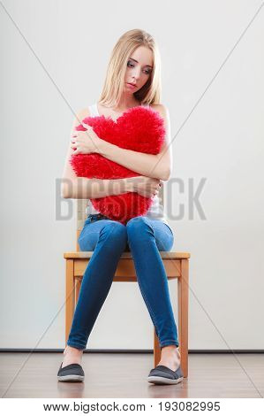 Broken heart love concept. Sad unhappy woman hugging red heart pillow