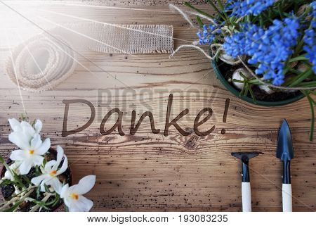 German Text Danke Means Thank You. Sunny Spring Flowers Like Grape Hyacinth And Crocus. Gardening Tools Like Rake And Shovel. Hemp Fabric Ribbon. Aged Wooden Background