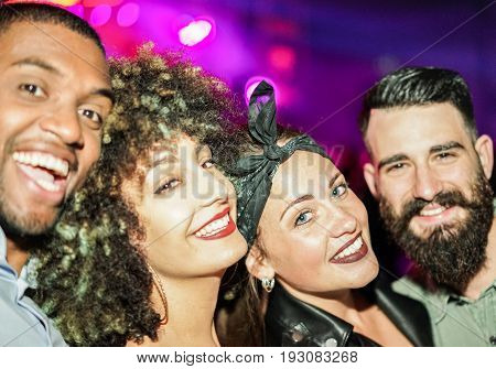 Happy friends taking selfie in night club dance floor - Young people enjoying weekend nightlife and having fun together - Soft focus on right woman eye - Youth and concept - Unfiltered flash photo