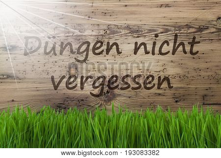 German Text Duengen Nicht Vergessen Means Dont Forget To Dung. Spring Season Greeting Card. Sunny Aged Wooden Background With Gras.