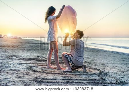 Young couple of lovers lighting sky lantern on the beach at sunset - Two lovers celebrating their anniversary in summer vacation - Love and travel concept - Soft focus on man hand - Contrast filter