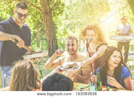 Happy friends having fun at barbecue party drinking beer eating listening music - Young people enjoying bbq dinner outdoor - Friendship and summer concept - Warm filter - Focus on center blond guys
