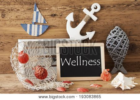 Blackboard With Nautical Summer Decoration And Wooden Background. English Text Wellness. Fish, Anchor, Shells And Fishnet For Maritime Contex.