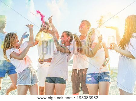 Happy friends partying with colorful powder cloud at holi festival in summer time - Young people having fun on the beach party - Youth and friendship concept - Focus on center girls face - Warm filter