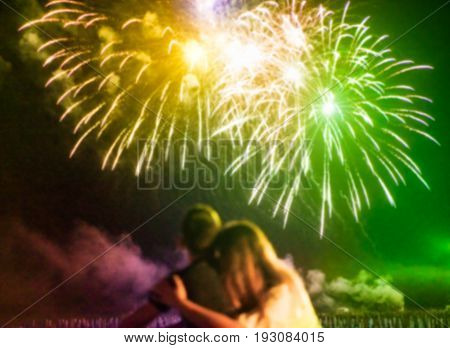 Blurred couple watching firework on top of the roof outdoor - Young lovers having romantic tender moments on the beach at festival summer event - Love and romance concept - Defocused image