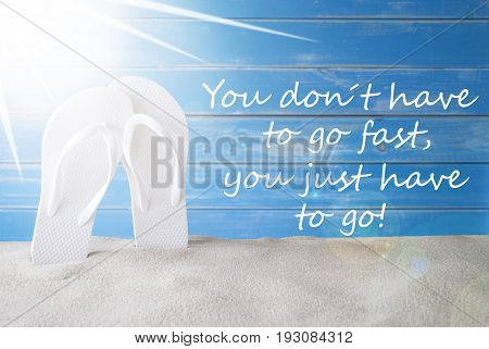 English Quote You Dont Have To Go Fast, You Just Have To Go. Sunny Summer Greeting Card With Sand And Flip Flops. Blue Vintage And Shabby Chic Wooden Background.