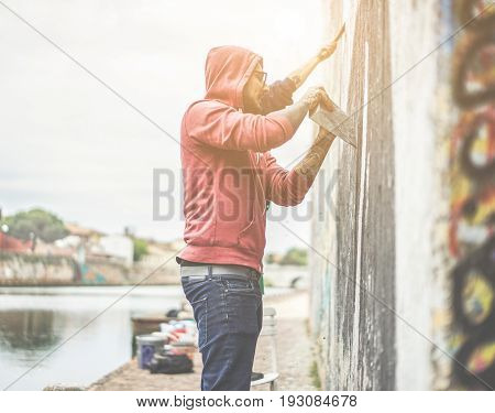 Two graffiti writers scraping the wall before painting their own picture - Contemporary artists at work - Urban lifestyle illegal street art concept - Focus on first man eyeglasses - Warm filter