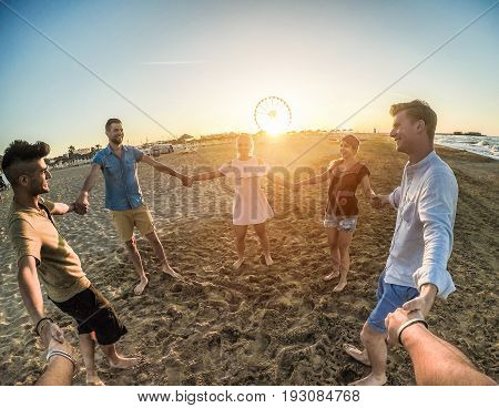Firsthand view of happy friends having fun on the beach party at sunset - Young trendy people laughing at party outdoor - Friendship travel concept - Soft focus on right man face - Contrast filter