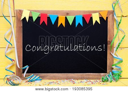 Blackboard With English Text Congratulations. Party Decoration Like Streamer And Confetti. Yellow Wooden Background. Greeting Card For Celebrations