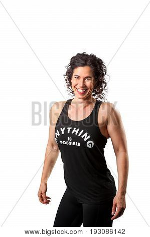 A beautiful muscular female trainer with dark curly hair poses for a portrait with a strong pose on a white background.