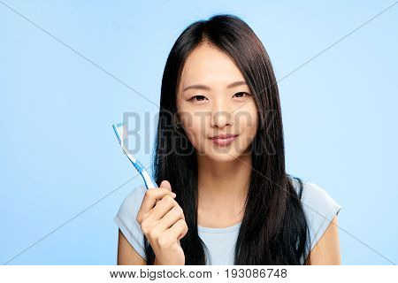 Asian woman on a blue background holds a toothbrush.