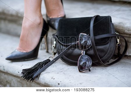 Beautiful colorful shoes, handbag and sunglasses for woman outdoors. Image with heel, bag and glasses for lady. Fashionable female boots. Style of outfit outside. Closeup legs of human