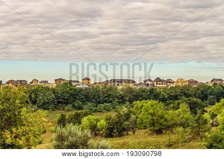 Evening suburban skyline. Buildings individual suburban housing in the eco-friendly green district. High layered clouds.