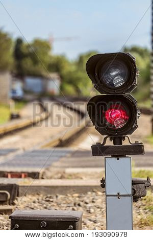Routing traffic light with a red signal on railway. Railway crossing with forbidding traffic signal. Limited depth of field.