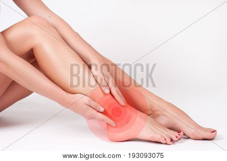 Ankle pain. Woman touching her injured foot. Female legs on white background poster