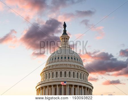 US flag flies in front of the US Capitol in Washington DC as the sun rises at dawn on a new day