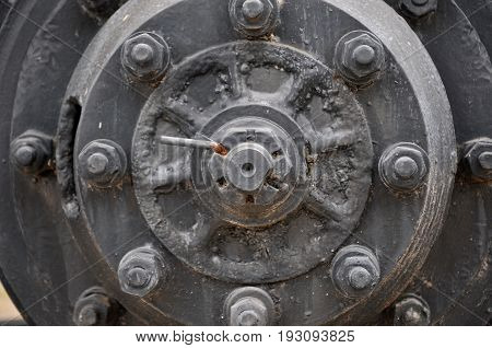 old truck wheel nut, large wheel with eight lugs nuts on metallic iron with rust wheel surface with centre cap of a heavy duty vehicle transport bus and truck