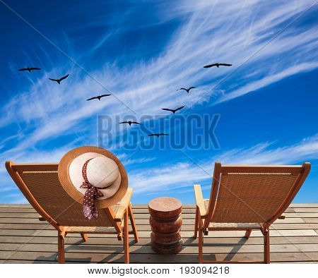Lovely place to relax. Two deck chairs and hat on a wooden platform. The concept of recreational tourism. Migratory birds flying high in the cirrus clouds