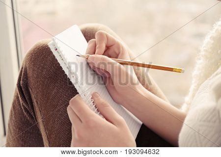 Beautiful young woman writing in notebook while sitting on window sill, closeup