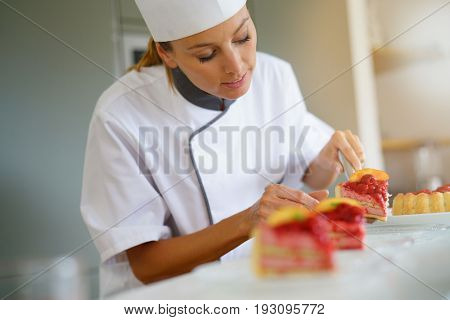 Portrait of pastry chef cutting slices of cake for serving