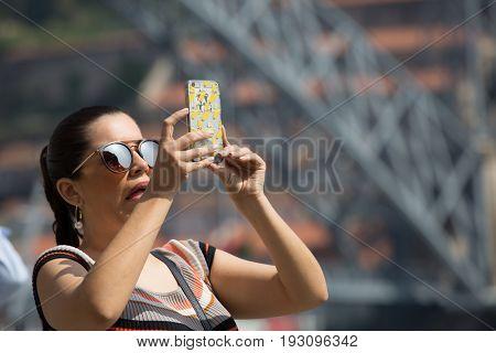 PORTO, PORTUGAL - APRIL 17, 2017: woman taking a picture at the Ribeira in the Douro River bank near the Dom Luis I Bridge, Porto, Portugal.