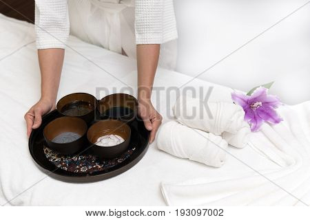 Hands of happy woman holding spa facial face mask in spa salon background Healthy lifestyle and relaxation concept