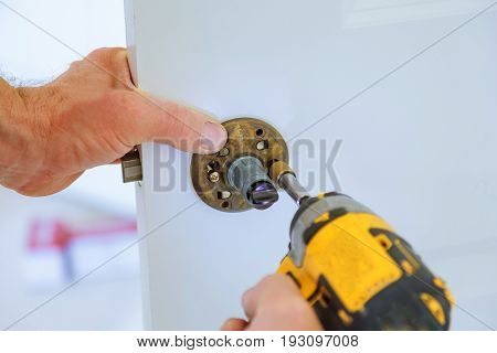Carpenter Lock Installation With Electric Drill Into Interior Wood Door