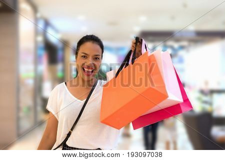 Shopping woman holding shopping bags in casual wear walking in trade center with copy space. Asian shopper smiling happy soft focus