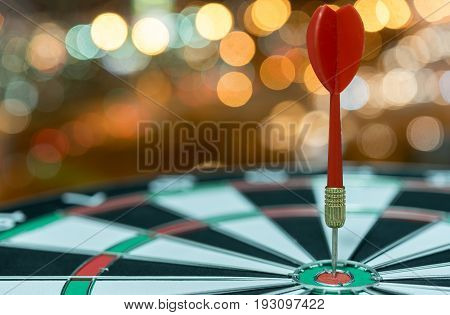 Red dart target arrow hitting on bullseye over bokeh light background vintage tonemetaphor to accuracy in business success concept