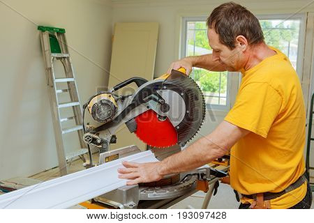 Contractor Using Circular Saw Cutting New Crown Moulding for Renovation.