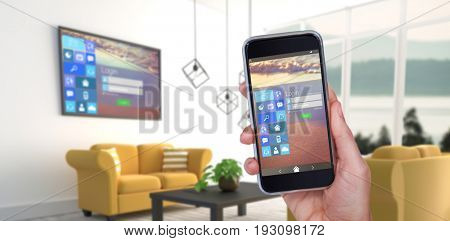 Hand holding mobile phone against white background against yellow sofas in modern living room