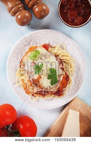 Chicken parmesan with melted cheese, tomato sauce and spaghetti pasta