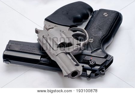A stainless revolver laying on top of a black semi automatic pistol
