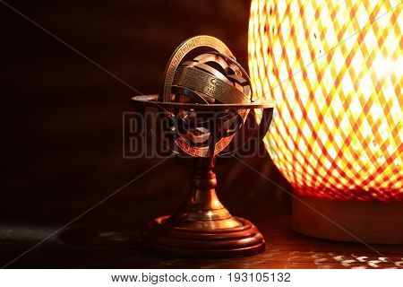 Vintage still life. Old brass globe and glowing lamp on dark background