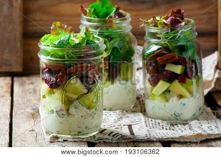 chicken apple and pecan salad in a jar.style rustic. selective focus