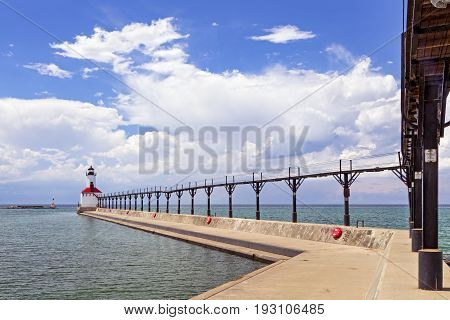 An elevated metal catwalk leads to the East Pierhead Lighthouse at Michigan City Indiana on a partly cloudy summer afternoon.
