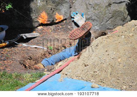 Male city utility worker repairing a broken sewage pipe underground.