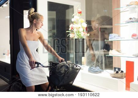 Casual young lady on bicycle wearing white summer dress window shopping in front of sinfully expensive boutique store dispaly window. Customer woman in shopping street looking at window an night.